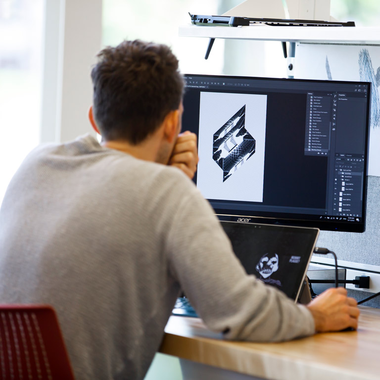 A student looks at a design on a computer screen.